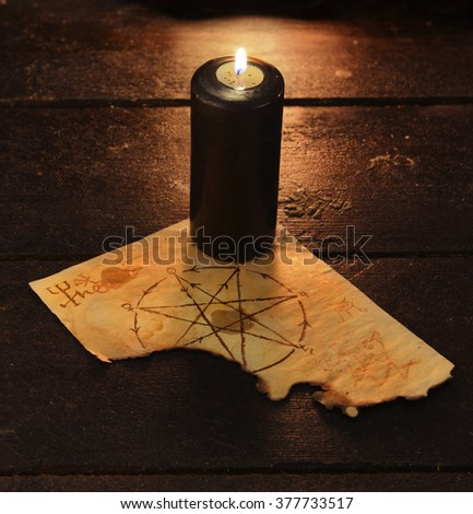 Black candle with pentagram on wooden table. Halloween and magic still life, fortune telling seance or black magic ritual with mysterious occult, evil and esoteric symbols  - stock photo