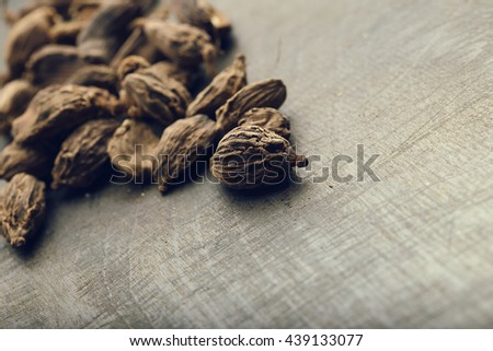 Black cardamom seeds on the wooden table. Aromatic, traditional ingredient for masala. Close-up. Toned image. - stock photo
