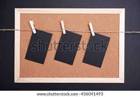 black cards hanged on a nylon thread. corkboard background.  - stock photo