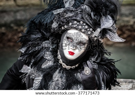 Black carnival mask wearing hat with long feathers, red lips and delicate tracery, Venice, Italy. - stock photo