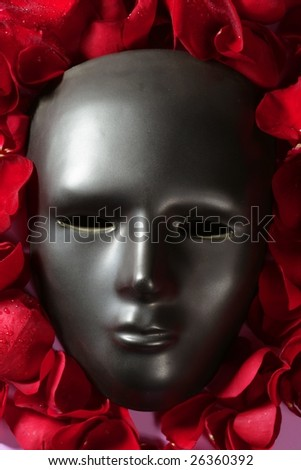 Black carnival mask with red rose petals around - stock photo