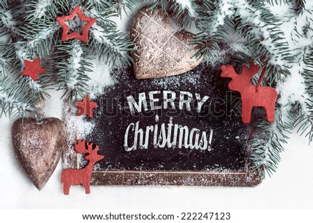 "Black chalkboard on snow with caption ""Merry Christmas!"" with wooden and and felt decorations - stock photo"