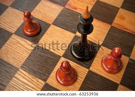 Black chess king surrounded with enemy pawns - stock photo