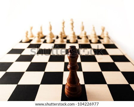 Black chess piece with a stretched perspective alone up against many white pieces. can stand for racism, challenge, adversity, diversity, courage,  or many other challenges in life. - stock photo
