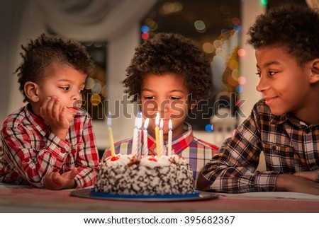 Black children with birthday cake. Three boys at birthday table. Happy birthday, brother. Watching the candles burn. - stock photo