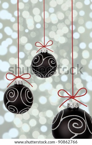black christmas baubles with ribbons on abstract light background - stock photo