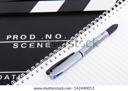 Black cinema clapper board and notebook for scenario with pen, isolated on white background. - stock photo