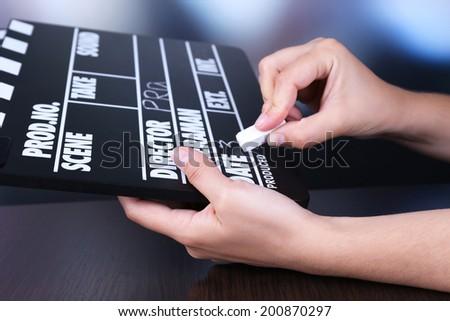 Black cinema clapper board in hands, close up - stock photo