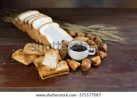 Black Coffee and many kind bread on old wooden plate / Still life style - stock photo