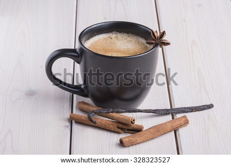 Black coffee cup with anise star, cinnamon and vanilia - stock photo