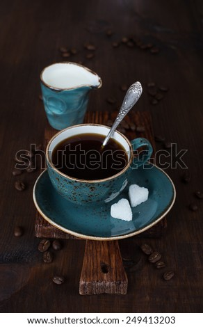 Black coffee in blue vintage cup with two pieces of refined sugar in the form of heart on old dark cutting board - stock photo