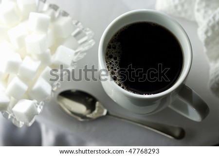 Black coffee in white cup with sugar cubes and spoon on white table cloth - stock photo