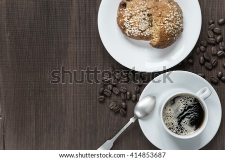 Black coffee with froth in white porcelain cup, coffee beans and oatmeal cookies on a dark wooden background, top view - stock photo