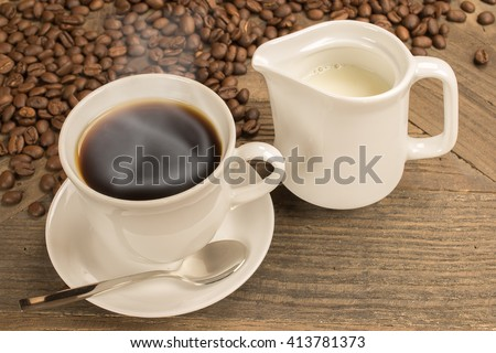 Black coffee with steam in white cup, jug with milk and fresh roasted coffee beans on rustic wooden table as background. - stock photo