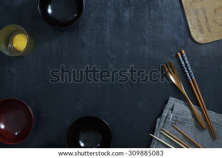 Black color wooden table top view. On the table are the Japanese wooden spoon, chopsticks, bowl,fresh raw eggs and table linen. - stock photo