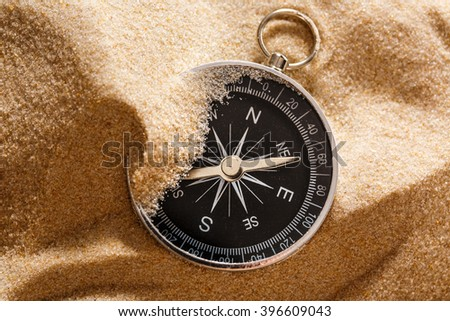Black compass with beach sand in closeup - stock photo