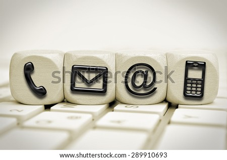 black contact us symbols on cubes on a keyboard - stock photo