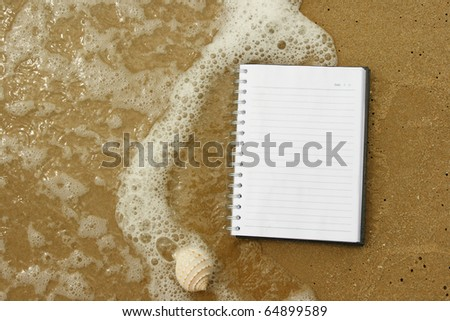 black cover of open white note book  on sand. - stock photo