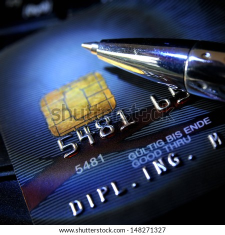Black credit card with ball pen on top - stock photo