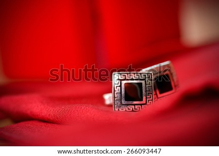 Black cufflinks for shirt in a nice red background - stock photo