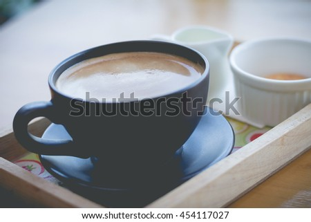 Black cup of coffee in afternoon break. coffee mocha on the wood desk. (selective focus vintage effect) - stock photo