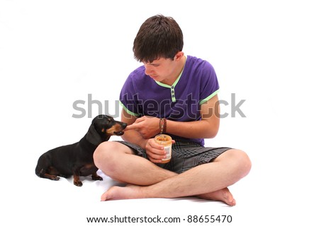 Black Dachshund dog enjoying peanut butter from young Caucasian boy's finger - stock photo