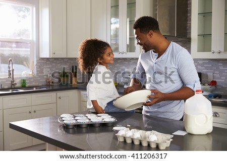Black dad and young daughter look at each other while baking - stock photo
