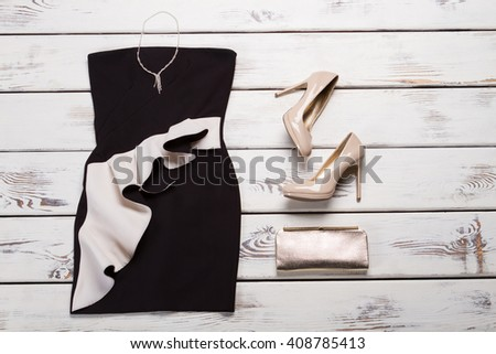 Black dress and beige heels. Dark evening dress on shelf. Female evening apparel with footwear. Luxury outfit in local store. - stock photo
