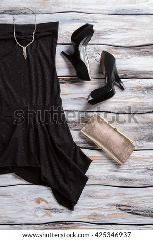 Black dress and silver purse. Dark heel shoes and jewelry. Luxury clothing for young ladies. Charm and elegance. - stock photo