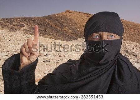 black dressed and veiled muslim woman raising her right index finger in front of mountains in the desert of of an islamic state. concept for religious behavior of muslim people - stock photo