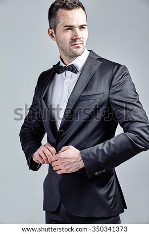 Black dressed man closing his jacket isolated over grey - stock photo