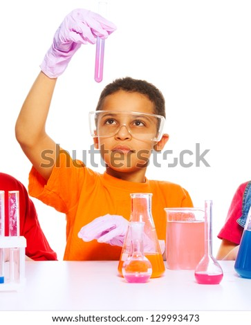 Black eight years old boy analyzing results of science test in the test tube - stock photo