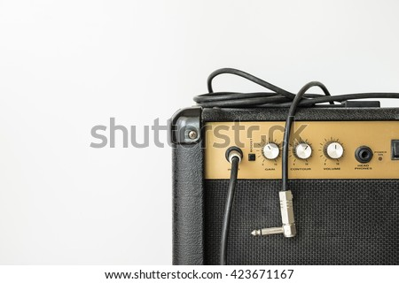 Black electric amplifier with cable on white background - stock photo