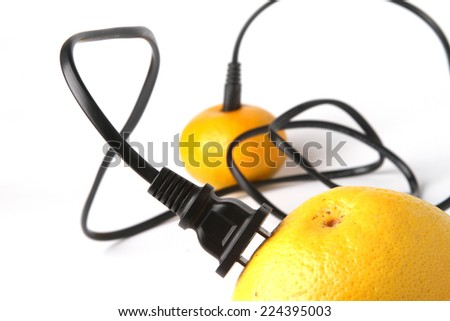 Black electric cable stab in fresh yellow grapefruit - save the earth - save the planet - energy - ecology - connect - green energy - nature energy  , , - stock photo