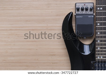 black electric guitar and distortion unit on a wooden background texture - stock photo