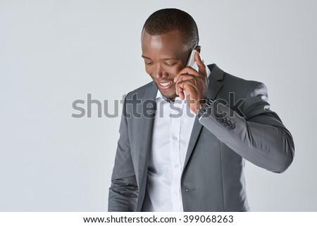 Black executive businessman talking on his smartphone having a conversation in studio - stock photo