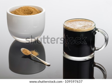 Black expresso coffee in small glass cup with sugar in white bowl reflecting - stock photo