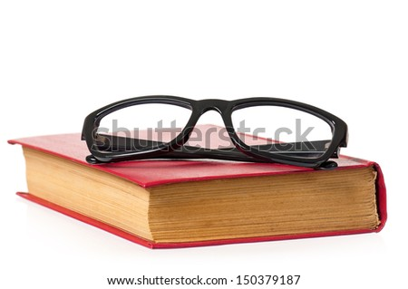 Black eye glasses and old book isolated on white background - stock photo