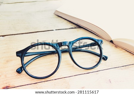 black eye glasses with a book, selected focus on glasses, in vintage style. - stock photo