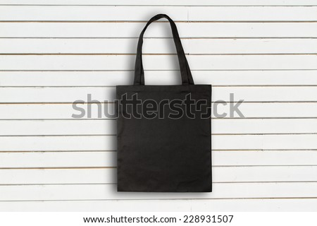 Black fabric bag against white wooden wall - stock photo