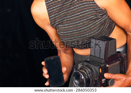 Black female photographer comparing new and old technology - stock photo