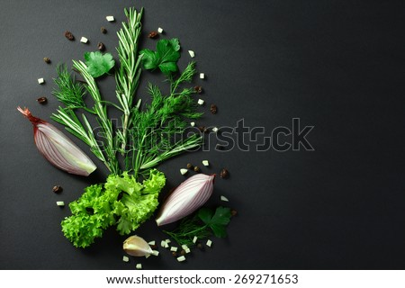 Black food background with fresh aromatic herbs and spices, copy space, top view - stock photo