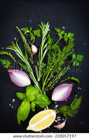 Black food background with fresh aromatic herbs. red onion and lemon, top view - stock photo