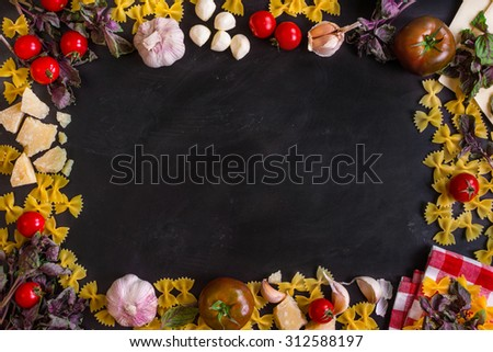 Black food background with italian food ingredients. Pasta, tomatoes, parmesan, mozzarella, basil, garlic on a rustic chalkboard - stock photo