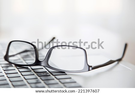 Black framed upside down glasses on the computer keyboard with a very shallow depth of field. - stock photo