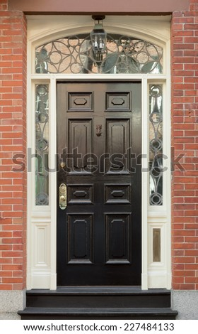 Black Front Door and Surrounding White Door Frame with Ornate Windows in Brick Building - stock photo