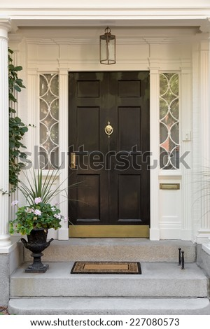 Black Front Door with White Door Frame and Side Windows over Steps with Potted Plant - stock photo