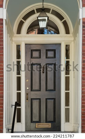 Black Front Door with Windows in Surrounding White Door Frame - stock photo