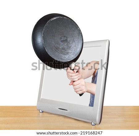 black frying pan in female hands leans out TV screen isolated on white background - stock photo