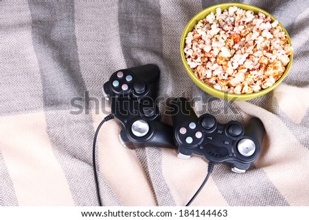 Black game controllers and bowl with pop corn on color plaid background - stock photo